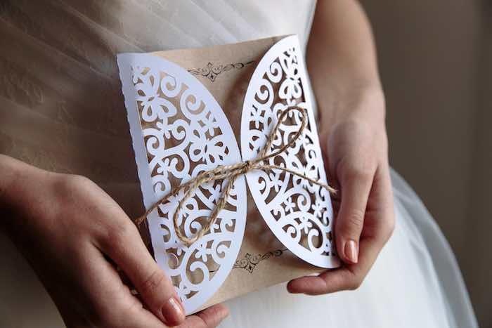 Rustic Wedding Invitations in the bride's hands.